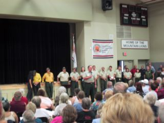 Forest Service, CalFire and Idy Fire folks speak to an anxious crowd in the Idyllwild School gym.
